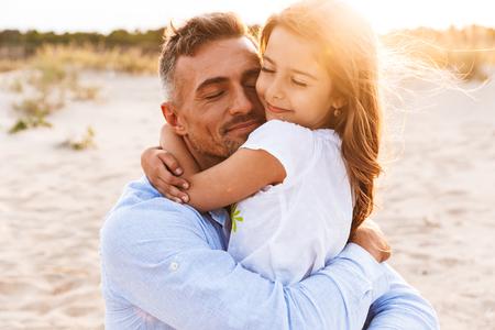 Gelukkig vader leuke tijd doorbrengen met zijn dochtertje op het strand, knuffelen Stockfoto