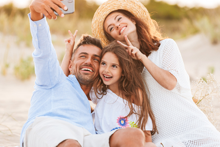 Image of young cute happy family having fun together outdoors at the beach make selfie by mobile phone showing peace gesture.