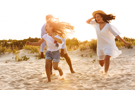 Image of young cute family having fun together outdoors at the beach.