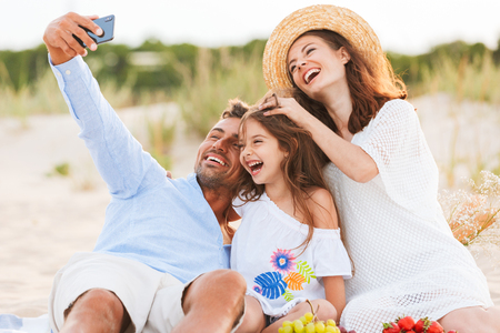 Image of young cute happy family having fun together outdoors at the beach make selfie by mobile phone.