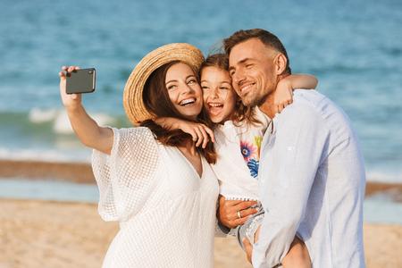 Familia feliz pasando un buen rato en la playa juntos, tomando selfie Foto de archivo