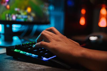Ręce człowieka profesjonalnego gracza, grając w gry wideo na komputerze w ciemnym pokoju przy użyciu podświetlanej klawiatury kolorowej