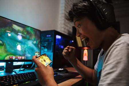 Asian gamer boy screaming while playing video games on smartphone and computer in dark room wearing headphones and using backlit colorful keyboard