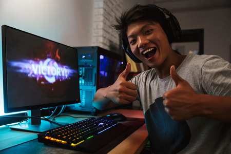 Young asian gamer boy rejoicing victory while playing video games on computer in dark room wearing headphones and using backlit colorful keyboard Stock Photo