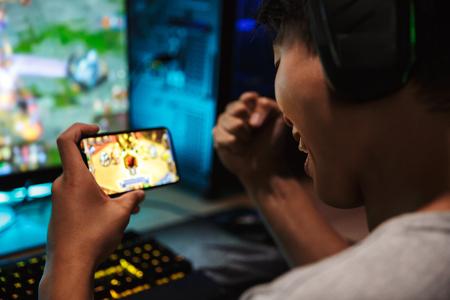Imagen de un joven jugador adolescente jugando videojuegos en un teléfono inteligente y una computadora en una habitación oscura usando audífonos y usando un teclado arco iris retroiluminado