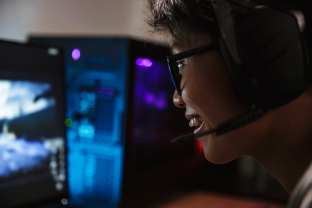 Photo closeup of asian pleased gamer boy playing video games online on computer in dark room wearing headphones with microphone and using backlit colorful keyboard