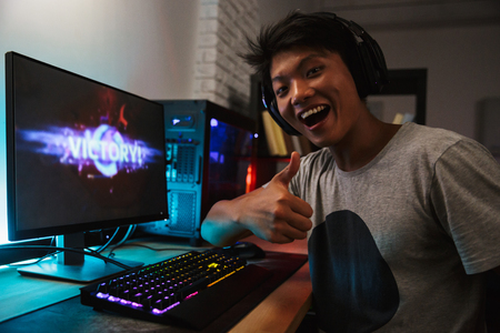 Happy asian gamer guy 16-18 rejoicing victory while playing video games on computer in dark room wearing headphones and using backlit colorful keyboard Stock Photo