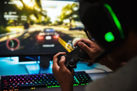 Foto-Nahaufnahme des jugendlichen Spielers, der Videospiele online auf Computer in dunklem Raum spielt, Kopfhörer mit Mikrofon tragend und Joystick verwendet