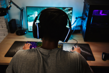 Back view of teenage gamer boy playing video games online on computer in dark room wearing headphones with microphone and using backlit colorful keyboard Foto de archivo - 107576481