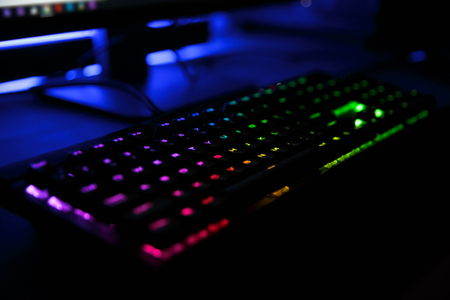 Close up view of workplace with led rainbow backlight gaming usb keyboard of computer lying on table in dark room 版權商用圖片 - 107580444