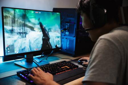 Portret azjatyckiego szczęśliwego chłopca gracza grającego w gry wideo online na komputerze w ciemnym pokoju na sobie słuchawki z mikrofonem i za pomocą podświetlanej klawiatury kolorowej Zdjęcie Seryjne