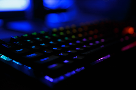 Closeup photo of workplace with led rainbow backlight gaming usb keyboard of computer lying on table in dark room Stock Photo