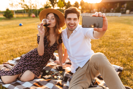 Photo of young cute loving couple sitting by dating outdors on picnic holding glasses of wine take a selfie by mobile phone.