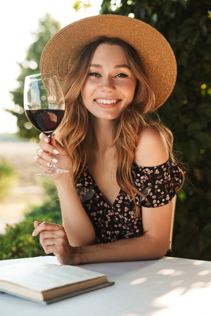 Image of cute pretty young woman sitting in cafe outdors in park with book holding glass drinking wine. Фото со стока