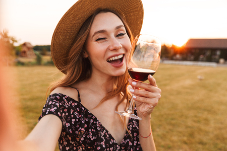Image of cute pretty young woman outdoors holding glass drinking wine make a selfie by camera winking.