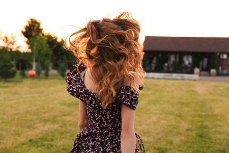 Back view photo of caucasian woman walking outdoor on green grass near restaurant or country house
