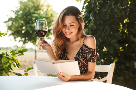 Photo of beautiful young woman sitting in cafe outdors in park with book holding glass drinking wine.