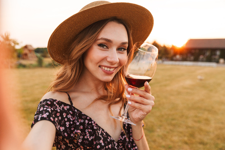 Image of cute pretty young woman outdoors holding glass drinking wine make a selfie by camera.