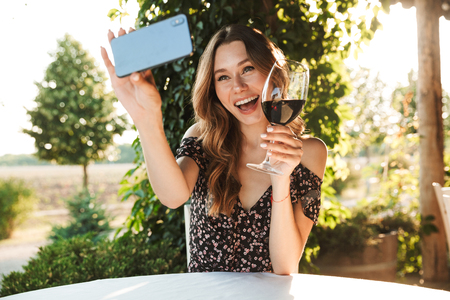 Picture of young woman sitting in cafe outdors in park holding glass drinking wine take a selfie by mobile phone. 版權商用圖片