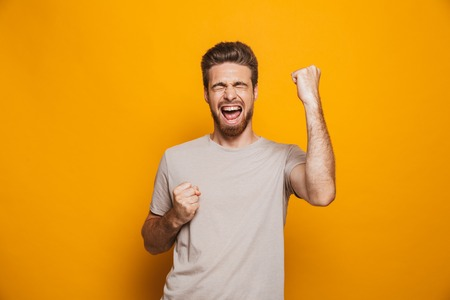 Image of handsome happy man standing isolated over yellow wall backgroung make a winner gesture.