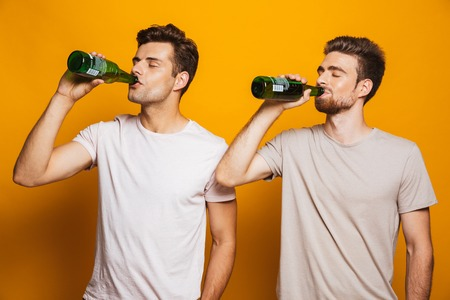Image of two handsome men friends standing isolated over yellow wall backgroung drinking beer.