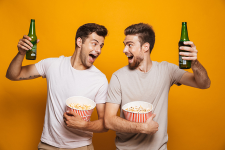 Image of two excited emotional handsome men friends standing isolated over yellow wall backgroung drinking beer eating popcorn.