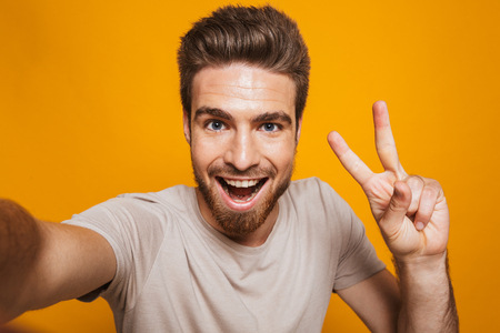 Image of handsome happy man standing isolated over yellow wall backgroung make a selfie by camera with peace gesture.