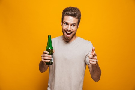 Image of handsome man standing isolated over yellow wall backgroung drinking beer pointing to you looking at camera.