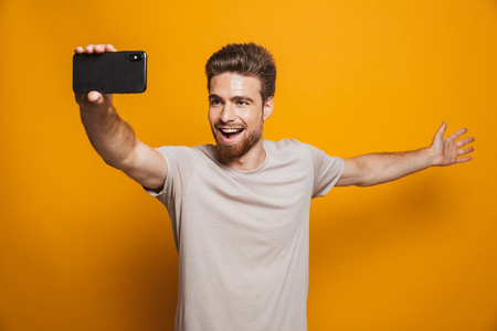 Image of handsome cheerful man standing isolated over yellow wall backgroung make a selfie by smartphone showing copyspace.