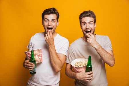 Image of two excited emotional handsome men friends standing isolated over yellow wall backgroung drinking beer eating popcorn looking camera.