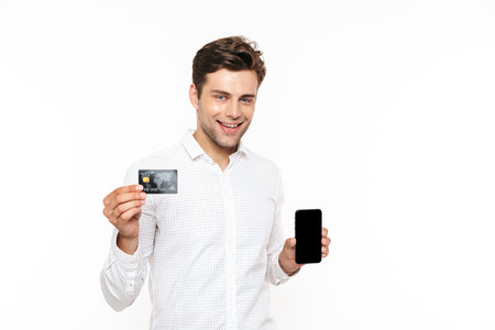Cheerful man with dark hair smiling while holding smartphone and credit card isolated over white background Stock Photo
