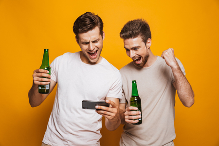 Image of two handsome men friends standing isolated over yellow wall backgroung drinking beer using mobile phone make winner gesture.