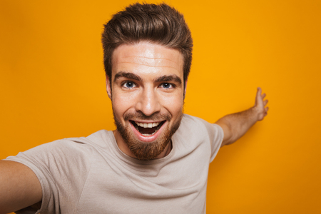 Image of handsome happy man standing isolated over yellow wall backgroung make a selfie by camera. Фото со стока
