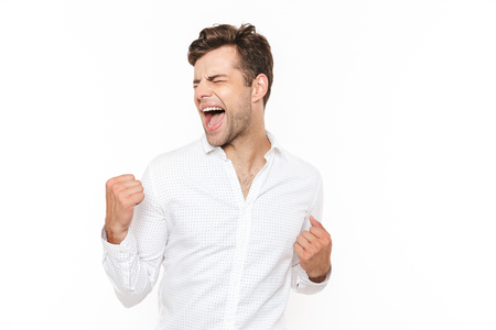 Photo of happy man 30s rejoicing and clenching fists isolated over white background