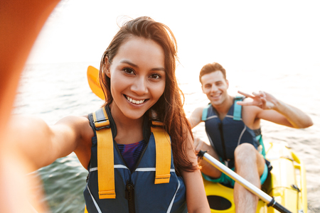 Image of young cute loving couple kayaking on lake sea in boat make selfie by camera.