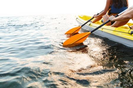 Beschnittenes Bild eines jungen Paares, das zusammen auf See kajakfährt