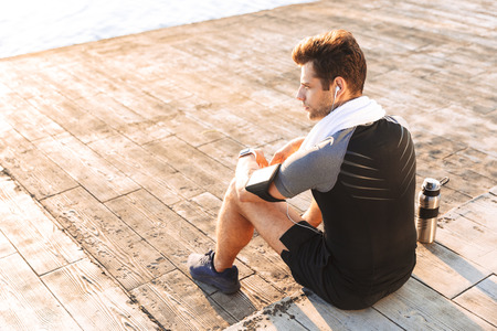 Photo of adult sportsman 20s in tracksuit listening to music via wireless headphones while sitting on wooden pier with thermos mug at seaside