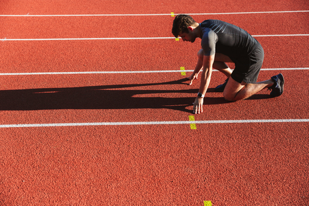 Side view of motivated young sportsman getting ready to run at the stadium Stock Photo