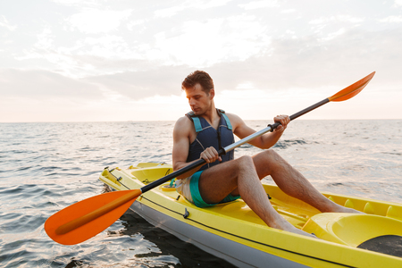 Image of young handsome man kayaking on lake sea in boat.