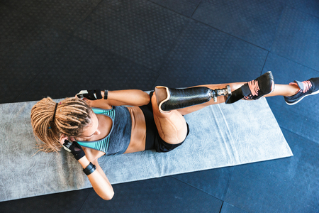 Portrait from above of fitness handicapped sportsgirl with prosthesis in tracksuit lying on mat and doing criss cross crunches in gym