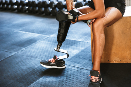 Cropped image of fitness disabled invalid woman wearing prosthesis in tracksuit training and lifting dumbbell in gym Zdjęcie Seryjne