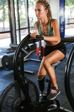 Portrait of athletic handicapped woman in tracksuit working out and doing crossfit exercises on training simulator in gym