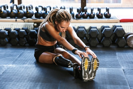 Image of strong disabled sports woman make sport stretching exercises in gym.