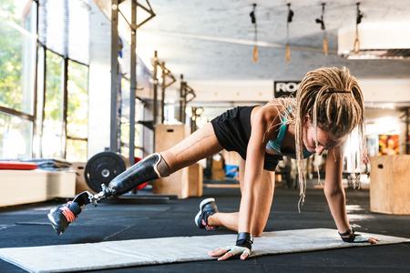 L'immagine della donna di sport disabili forte incredibile fa esercizi sportivi in palestra