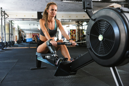 Portrait of athletic handicapped woman with prosthesis in tracksuit working out and doing crossfit exercises on training simulator in gym