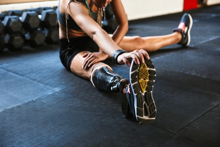 Cropped image of strong disabled sports woman make sport stretching exercises in gym. Stock Photo