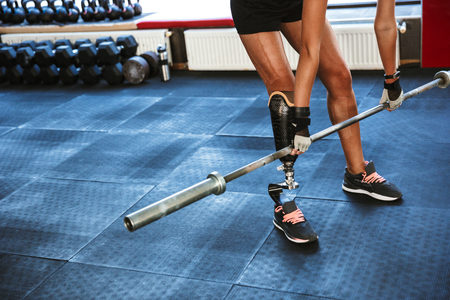 Cropped image of amazing strong disabled sports woman make sport exercises with barbell equipment in gym.