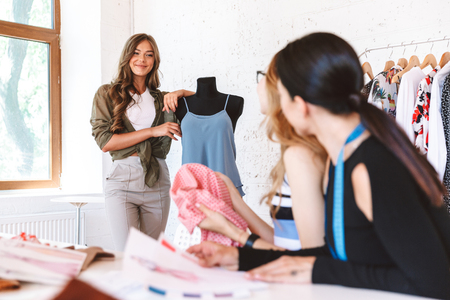 Smiling young woman clothes designer teaching colleagues at the atelier studio Stock Photo