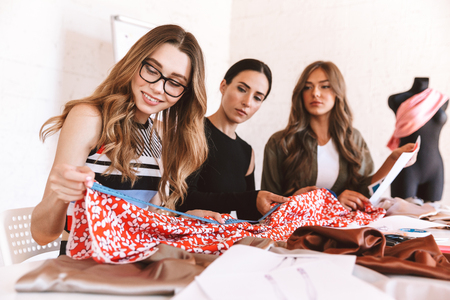 Three attractive young women clothes designers working together at the atelier, sitting at the table Stock Photo