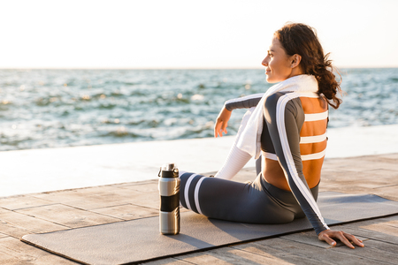 Image of beautiful young fitness woman outdoors on the beach have a rest sitting with towel and water.